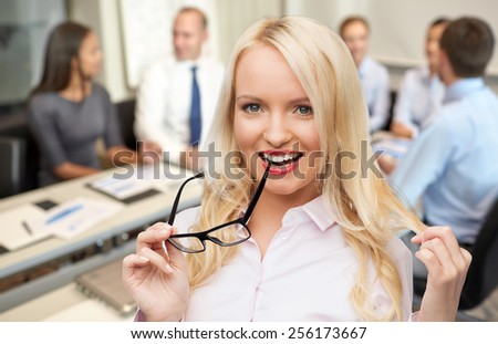 business, teamwork and people concept - smiling businesswoman, student or secretary with eyeglasses over office and group of colleagues background - stock photo