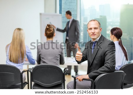 business, teamwork, people and success concept - confident businessman with team in office showing thumbs up - stock photo