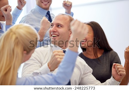 business, teamwork, people and success concept - smiling business team making triumph gesture in office - stock photo