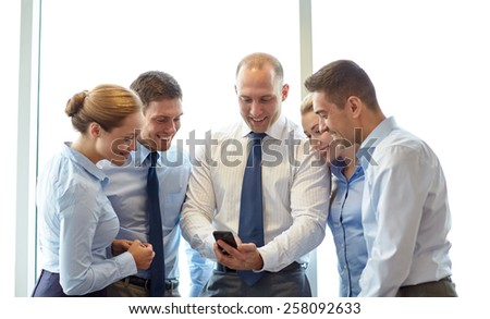 business, teamwork, people and technology concept - business team with smartphone meeting in office - stock photo