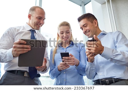 business, teamwork, people and technology concept - business team with tablet pc and smartphones meeting in office - stock photo