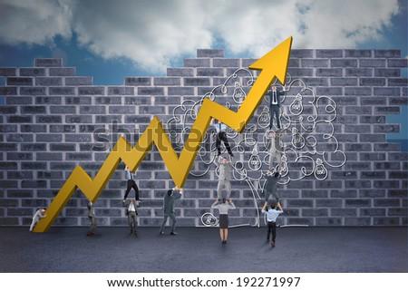 Business teamwork pushing arrow against light bulb tree doodle against wall - stock photo