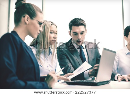 business, technology and office concept - concentrated business team with laptop computers and documents having discussion in office - stock photo
