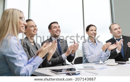 business, technology and office concept - happy business team with laptop computers, documents and coffee clapping hand - stock photo