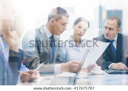business, technology and office concept - serious business team with laptop computers, documents and coffee having discussion in office - stock photo