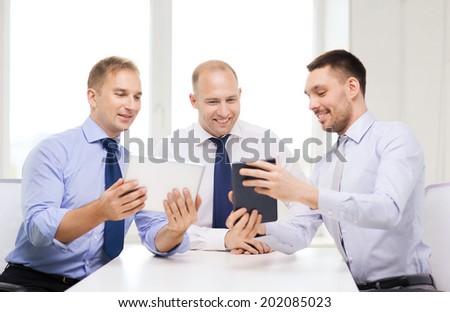 business, technology and office concept - three smiling businessmen with tablet pc computers in office - stock photo