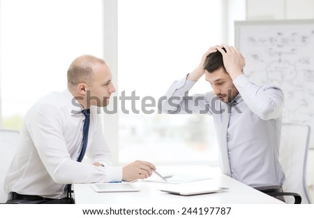 business, technology and office concept - two serious businessmen with tablet pc computers and files in office - stock photo
