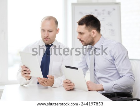 business, technology and office concept - two serious businessmen with tablet pc computers in office - stock photo