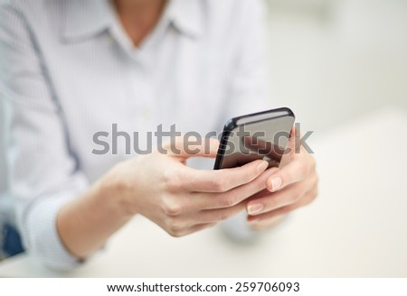 business, technology and people concept - close up of woman hands texting message on smartphone at office - stock photo