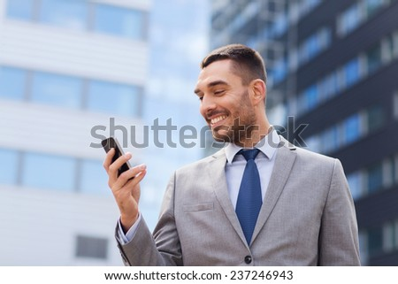 business, technology and people concept - smiling businessman with smartphone over office building - stock photo
