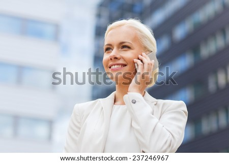 business, technology and people concept - smiling businesswoman with smartphone talking over office building - stock photo