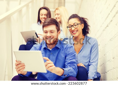business, technology and startup concept - smiling creative team with tablet pc computer sitting on staircase - stock photo