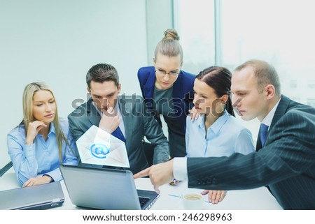 business, technology, communication and people concept - serious business team with laptop computers and email icon projection having discussion in office - stock photo