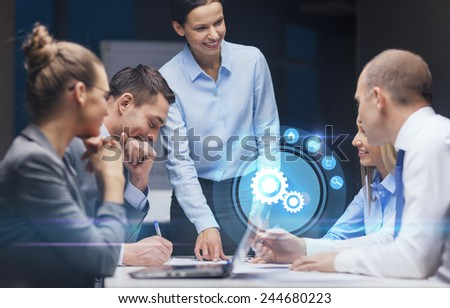 business, technology, deadline, management and people concept - smiling female boss talking to business team in office late night - stock photo