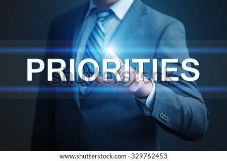 business, technology, internet and networking concept - businessman pressing priorities button on virtual screens - stock photo