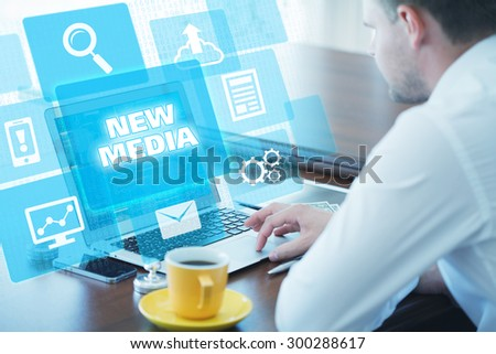 Business, technology, internet and networking concept. Young businessman working on his laptop in the office, select the icon new media on the virtual display - stock photo
