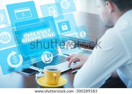 Business, technology, internet and networking concept. Young businessman working on his laptop in the office, select the icon internet marketing on the virtual display. - stock photo