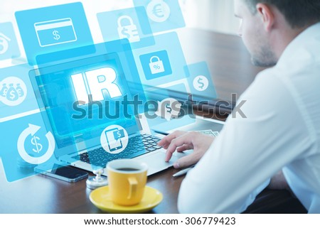 Business, technology, internet and networking concept. Young businessman working on his laptop in the office, select the icon IR â?? Interest Rate on the virtual display. - stock photo