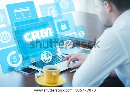 Business, technology, internet and networking concept. Young businessman working on his laptop in the office, select the icon CRM â?? Customer Relationship Management on the virtual display. - stock photo