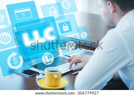 Business, technology, internet and networking concept. Young businessman working on his laptop in the office, select the icon LLC â?? Limited Liability Company on the virtual display. - stock photo
