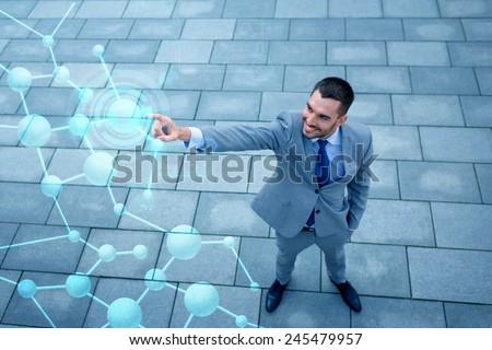 business, technology, internet connection and people concept - young smiling businessman pointing finger to virtual network projection outdoors from top - stock photo