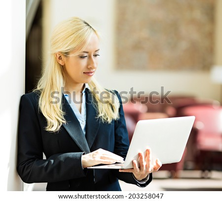 Business technology, internet hotel concept. Closeup portrait happy smiling businesswoman working on tablet pc computer checking email isolated background corporate office hallway. Positive expression - stock photo