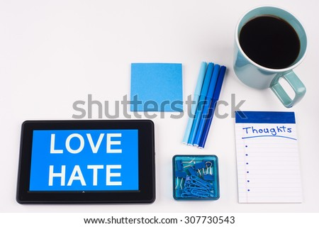Business Term / Business Phrase on Tablet PC - Blue Colors, Coffee, Pens, Paper Clips and note pads on White - White Word(s) on blue - Love Hate - stock photo