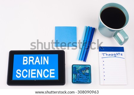 Business Term / Business Phrase on Tablet PC - Blue Colors, Coffee, Pens, Paper Clips and note pads on White - White Word(s) on blue - Brain Science - stock photo