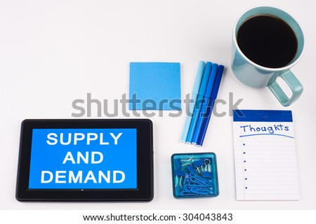Business Term / Business Phrase on Tablet PC - Blues, cup of coffee, Pens, paper clips Calculator with a blue note pad on White - White Word(s) on blue - Supply And Demand - stock photo