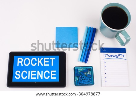 Business Term / Business Phrase on Tablet PC - Blues, cup of coffee, Pens, paper clips Calculator with a blue note pad on White - White Word(s) on blue - Rocket Science - stock photo