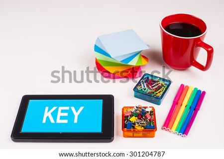 Business Term / Business Phrase on Tablet PC - Colorful Rainbow Colors, Cup, Notepad, Pens, Paper Clips, White surface - White Word(s) on a cyan background - Key - stock photo