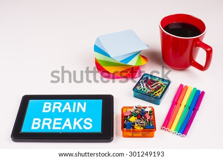 Business Term / Business Phrase on Tablet PC - Colorful Rainbow Colors, Cup, Notepad, Pens, Paper Clips, White surface - White Word(s) on a cyan background - Brain Breaks - stock photo