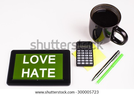 Business Term / Business Phrase on Tablet PC - Cup of coffee, Pens, Calculator and a green/yellow note pad on a White surface - White Word(s) on a green background - Love Hate - stock photo