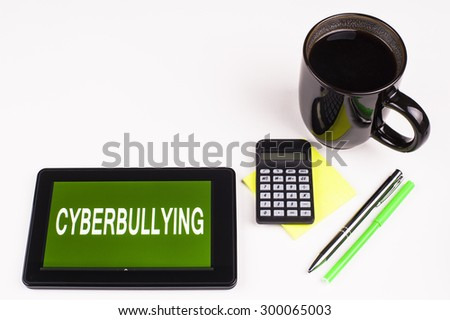 Business Term / Business Phrase on Tablet PC - Cup of coffee, Pens, Calculator and a green/yellow note pad on a White surface - White Word(s) on a green background - Cyberbullying - stock photo