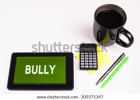 Business Term / Business Phrase on Tablet PC - Cup of coffee, Pens, Calculator and a green/yellow note pad on a White surface - White Word(s) on a green background - Bully - stock photo