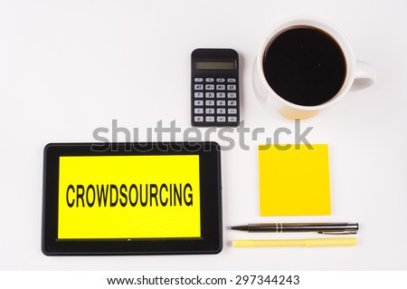 Business Term / Business Phrase on Tablet PC with a cup of coffee, Pens, Calculator, and yellow note pad on a White Background - Black Word(s) on a yellow background - Crowdsourcing - stock photo