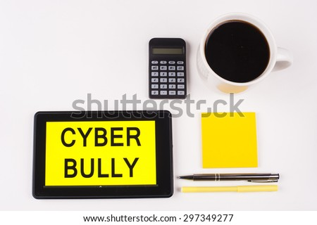 Business Term / Business Phrase on Tablet PC with a cup of coffee, Pens, Calculator, and yellow note pad on a White Background - Black Word(s) on a yellow background - Cyber Bully - stock photo
