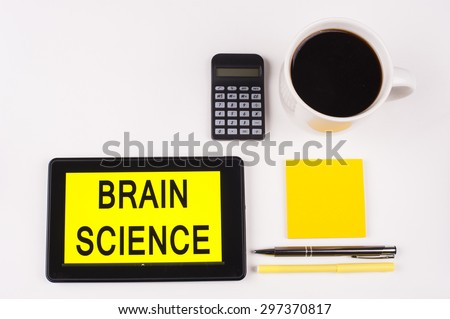 Business Term / Business Phrase on Tablet PC with a cup of coffee, Pens, Calculator, and yellow note pad on a White Background - Black Word(s) on a yellow background - Brain Science - stock photo