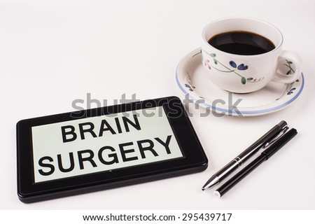 Business Term / Phrase on Tablet PC with a cup of coffee and pens on a White Background - Black Word(s) on a white background - Brain Surgery - stock photo