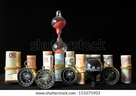 Business Time Concept Money and Hourglass on a Black Background - stock photo