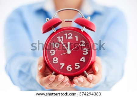 Business time concept. Woman holding red alarm clock in his hands close up. - stock photo