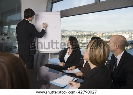 Business training where group of persons is wearing business clothes and sitting at a table with the teacher standing in front of a flip chart - stock photo
