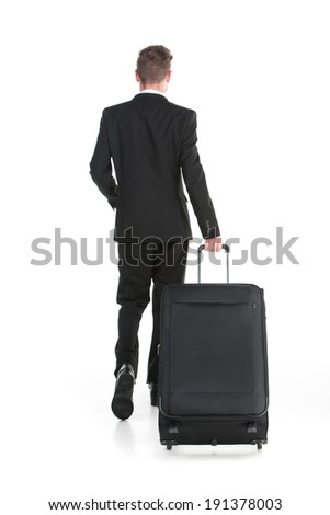 Business travel. Business traveler man walking with suitcase rear view - stock photo