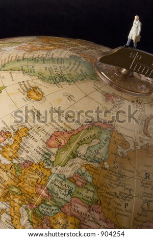 Business travel figure on globe with black background viewing europe - stock photo