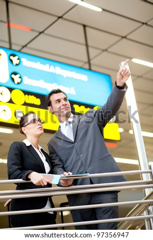 business travellers pointing at flight information board - stock photo