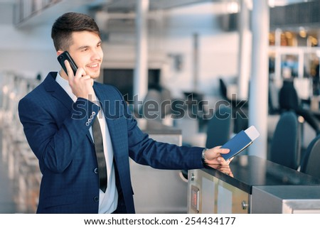 Business trip. Handsome young businessman in suit holding his passport and talking over his mobile phone while standing against airline check in counter in the airport - stock photo