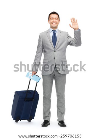 business trip, traveling, luggage and people concept - happy businessman in suit with travel bag and air ticket waving hand - stock photo
