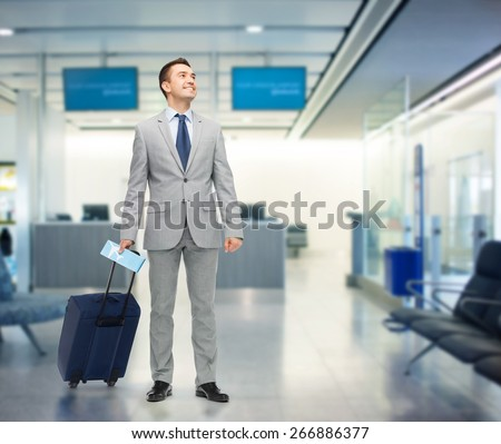 business trip, traveling, luggage and people concept - happy businessman in suit with travel bag and air ticket over airport background - stock photo