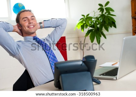 Business tycoon relaxing on his chair - stock photo