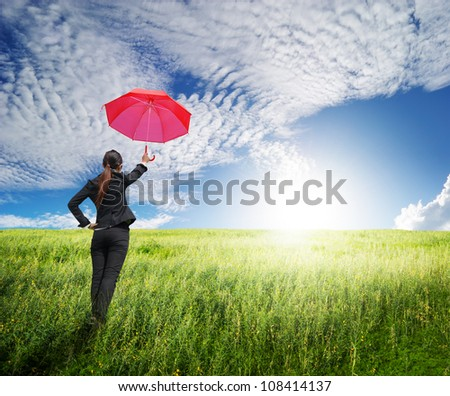 Business umbrella woman standing to blue sky in grassland with red umbrella - stock photo